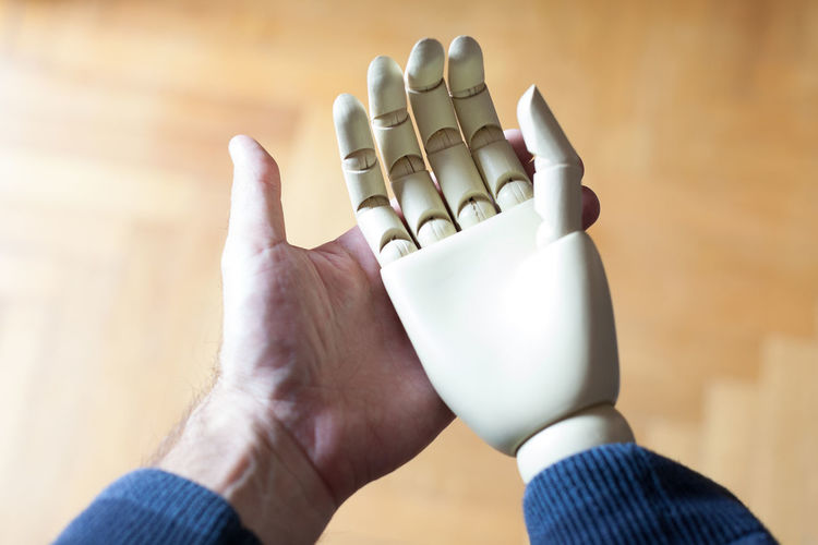 Cropped Image Of Man Holding Robot Hand