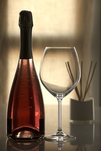 Close-up of red wine bottle and glass on table