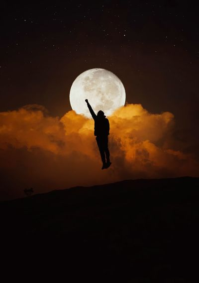 Silhouette man against moon at sunset