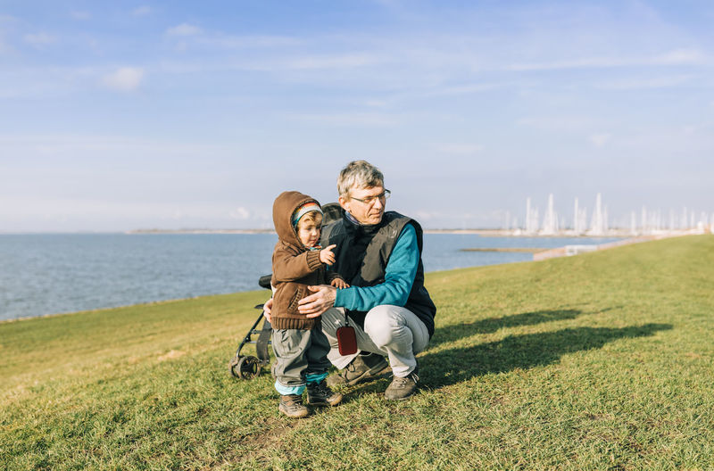 Toddler girl with grandfather on dyke of IJsselmeer – Hindeloopen, Netherlands, Europe Grandfather Grandchild Granddaughter Generations Multi-generation Family Offspring Vacations Dyke  Family❤ Family With One Child Lake Ijsselmeer Netherlands Field Crouching Pointing Care Happiness Exploring Showing Sweater Toddler  Girl First Steps Walking Togetherness Emotion Bonding Males  Water Family Adult Men Sea Childhood Sky Child Two People Nature Love Women Full Length Females Boys Positive Emotion Horizon Over Water