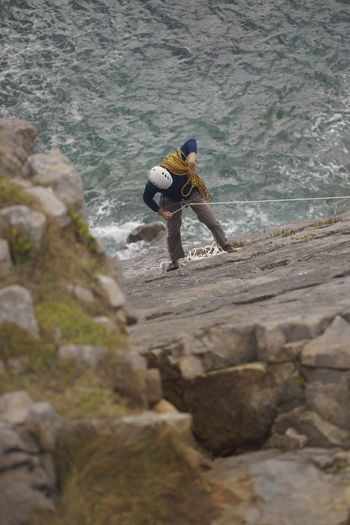 High angle view of man climbing on rock by sea