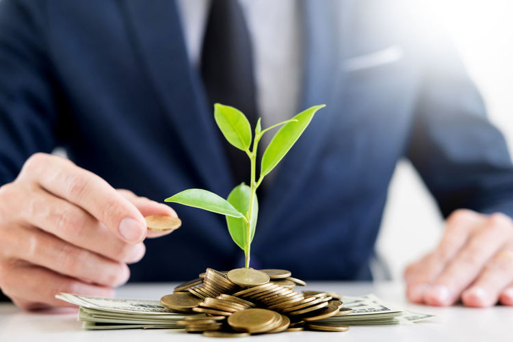 Midsection of businessman planting amidst coins at office