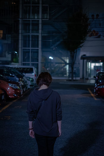 Rear view of woman standing on illuminated street at night