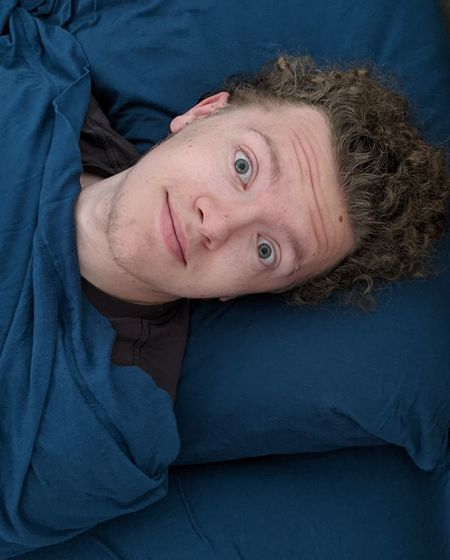 Portrait of man lying down on bed