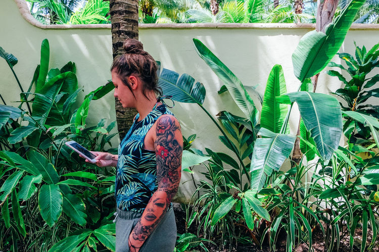 Side view of woman using mobile phone by plants