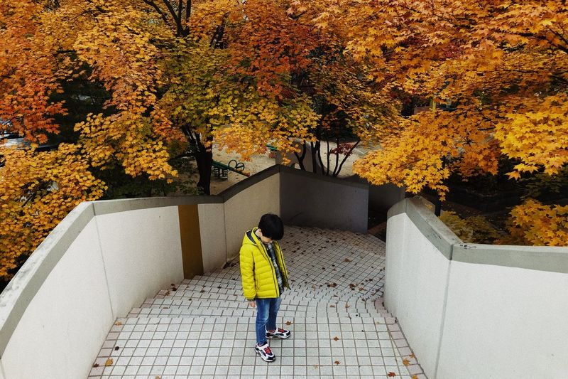 Full length of man walking on footpath during autumn