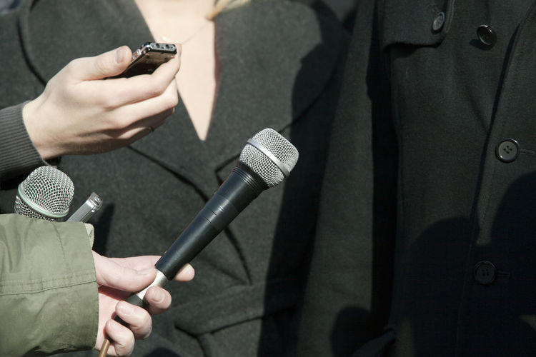 Cropped Hand Of Journalist Holding Microphone For People