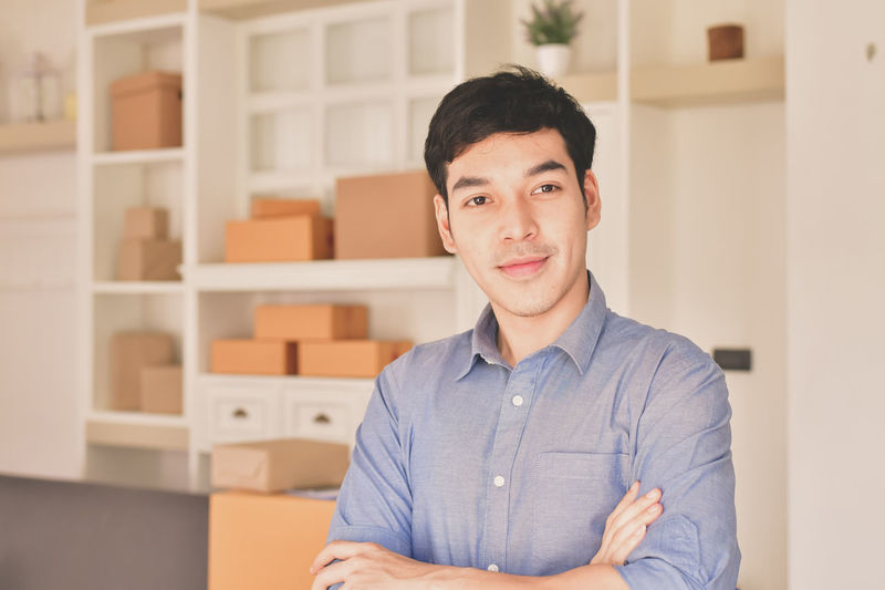 Adult Business Business Person Button Down Shirt Casual Clothing Confidence  Emotion Focus On Foreground Front View Headshot Indoors  Looking At Camera Office One Person Portrait Smiling Waist Up Young Adult