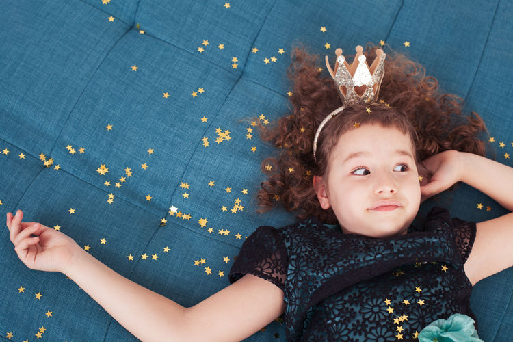 High Angle View Of Cute Girl Wearing Crown While Lying On Bed At Home