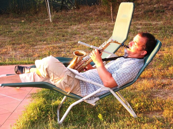 Side View Of Man Playing Saxophone While Relaxing On Lounge Chair At Grassy Field