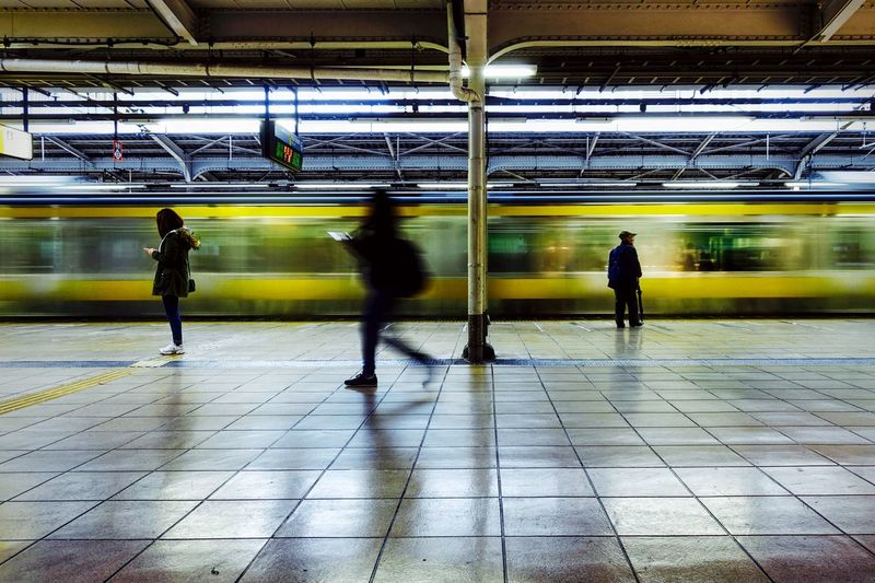 Blurred motion of train by people at railroad station platform