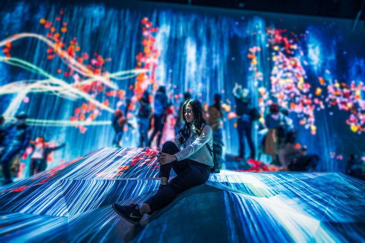 One Person Sitting Adult Illuminated Women City Full Length Motion Looking Technology Mid Adult Real People Architecture Night Young Adult Lifestyles Outdoors Three Quarter Length Casual Clothing Hairstyle Digital Composite TeamLabBorderless TeamLab