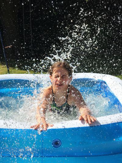 Girl Splashing Water In Wading Pool At Back Yard