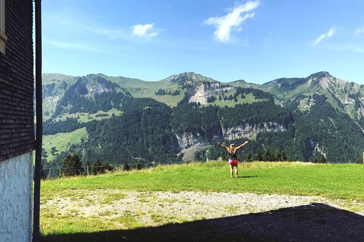 Woman on field by mountains against sky