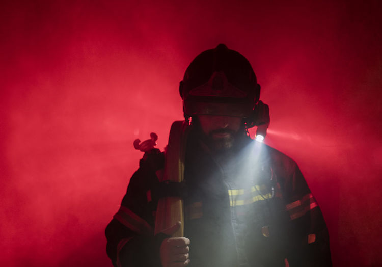 Close-up of firefighter against red light