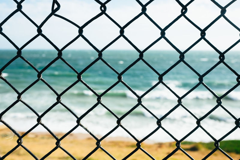 Through the fence. Architecture Backgrounds Barrier Behind The Fence Boundary Built Structure Chainlink Fence Close-up Crisscross Day Fence Focus On Foreground Full Frame Metal Nature No People Outdoors Pattern Protection Repetition Safety Sea Seascape Security See Through