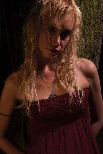 Portrait Of Woman Against Tree Trunk At Night