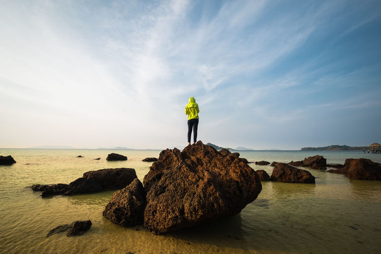Rear View Of Young Woman Standing On Rock In Sea Against Sky