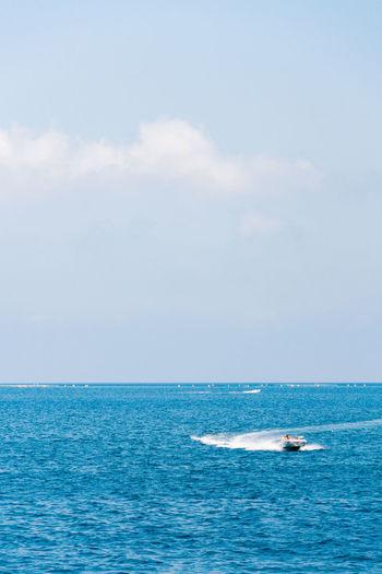 Boat splashing water in sea against sky