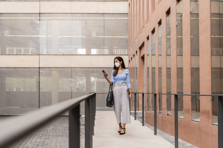 Full length of woman standing on railing against building