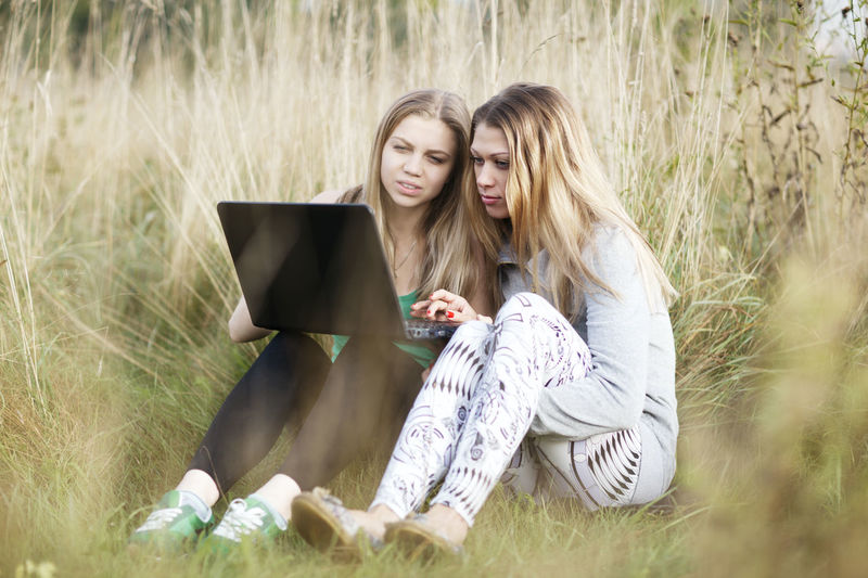 Full Length Of Sisters Using Laptop On Grassy Field