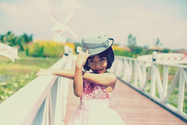 Girl looking away while standing on railing
