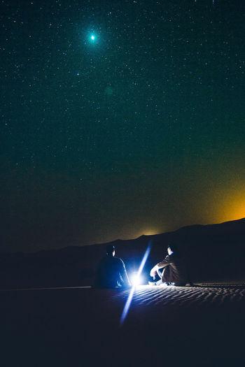 Silhouette man against illuminated sky at night