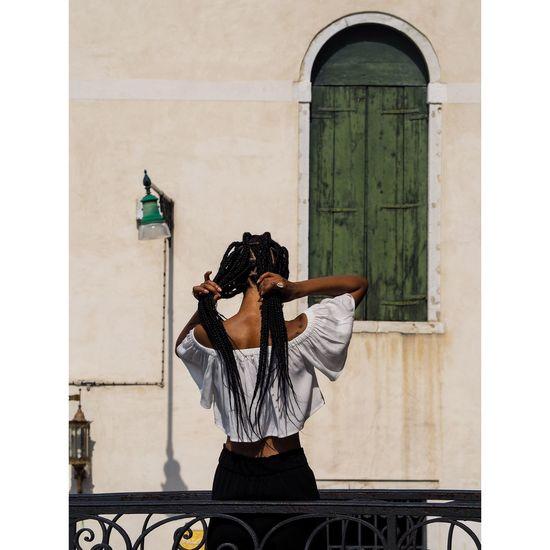 Rear view of woman adjusting hair against building