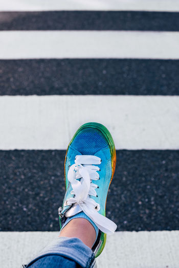 Low section of person wearing multi colored shoes walking on road