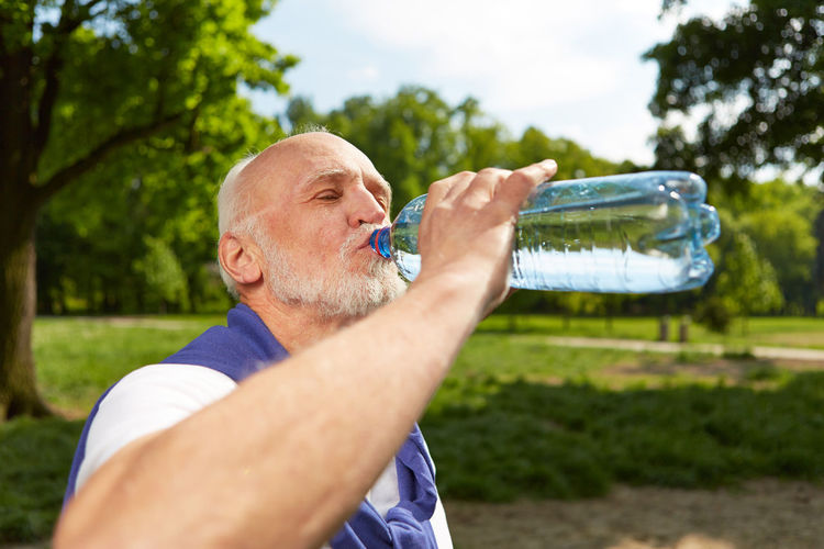 Close-Up Of Senior Man Drinking Water While Standing At Park