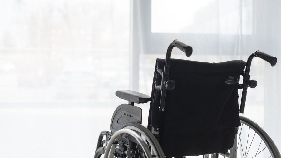 Empty wheelchair against window at home