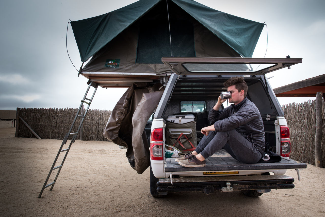 Man sitting in motor home and drinking coffee