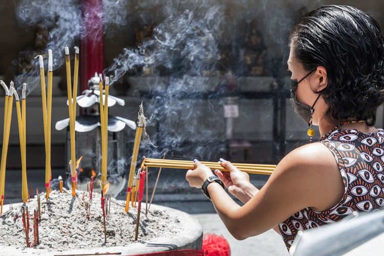 Side view of woman holding incense at temple