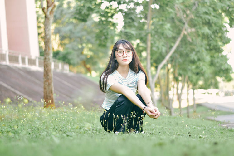 Portrait of young woman crouching on grass against tree at park