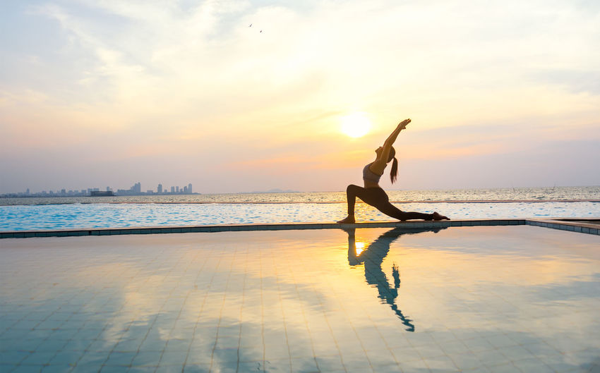 Woman exercising by sea against sky during sunset
