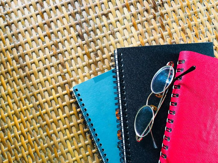 Directly Above Shot Of Spiral Notebooks And Eyeglasses On Wicker Table