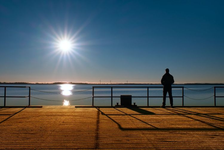 Man stand on wharf construction and looking at sea. sunny clear blue sky, smooth water level