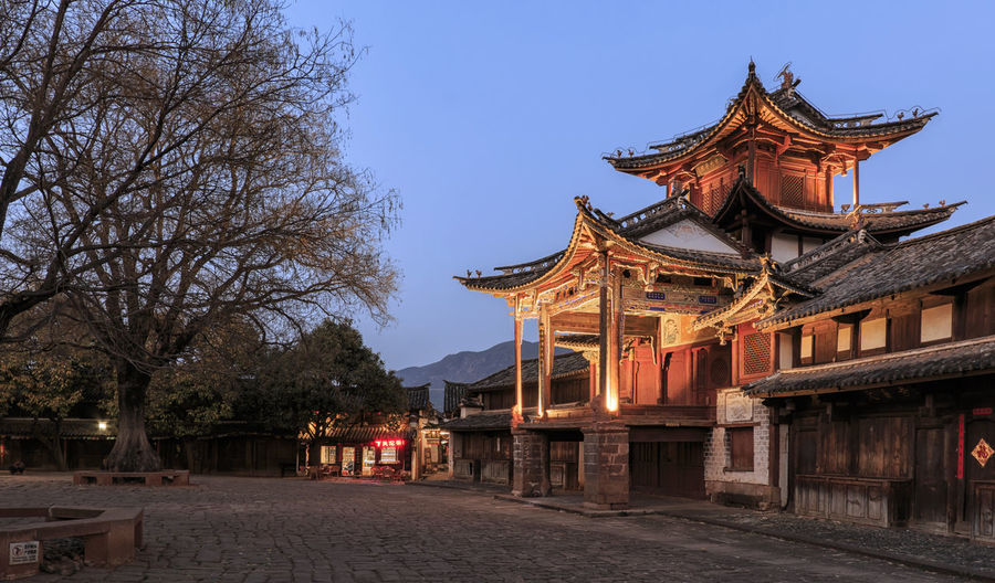 Shaxi, China - February 21, 2019: Central square of Shaxi old town at sunset with the old theater illuminated Shaxi China ASIA Yunnan Yunnan ,China Market South Silk Road Tea Horse Road Minority Ethnic Group Old Town Kunming, China Landscape People Night Teather Old