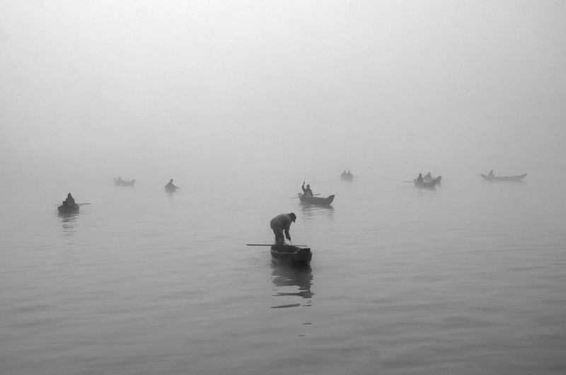 Man In Boat On River Against Sky During Foggy Weather