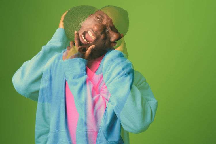 Double exposure of frustrated man against green background