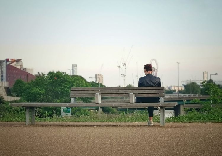 Man sitting on bench against clear sky