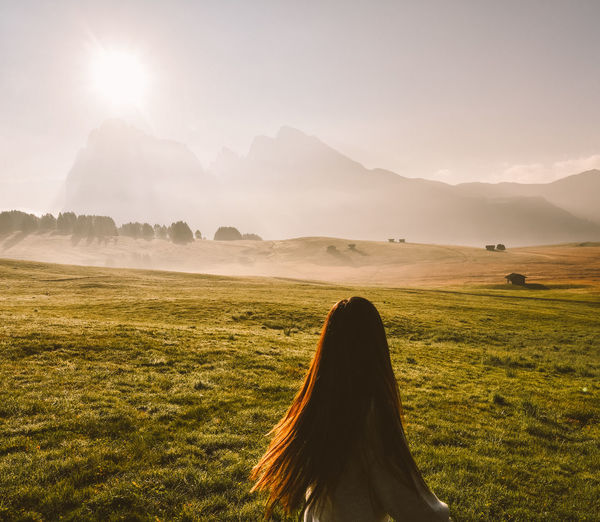 Rear view of woman standing on land during sunrise