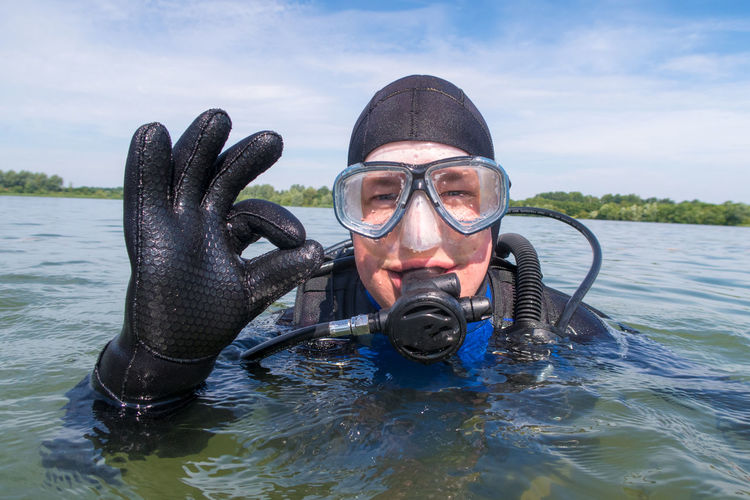 Portrait Of Scuba Diver Showing Ok Sign In Sea Against Sky