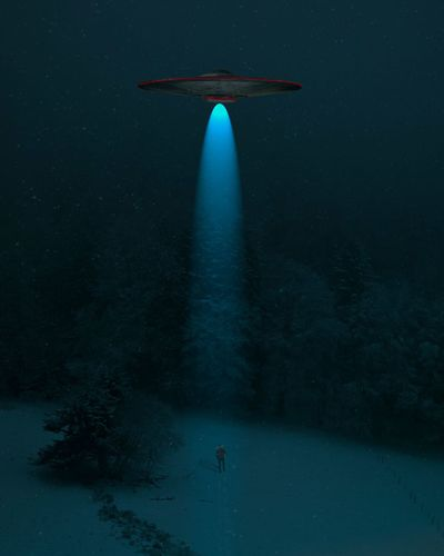 Illuminated spaceship in forest during winter at night