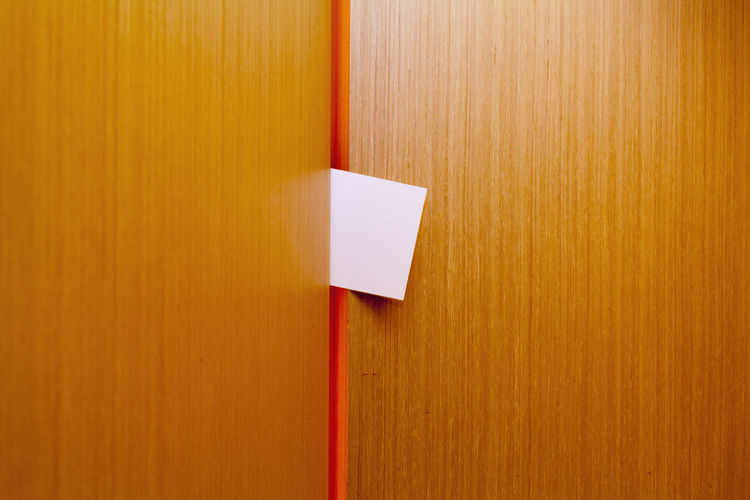 A note squeezed between wood panels Graphic Background Backgrounds Blank Close-up Day Indoors  Indoors  Message No People Note Paper Paper Textured  Wood - Material Wood Paneling Yellow EyeEmNewHere