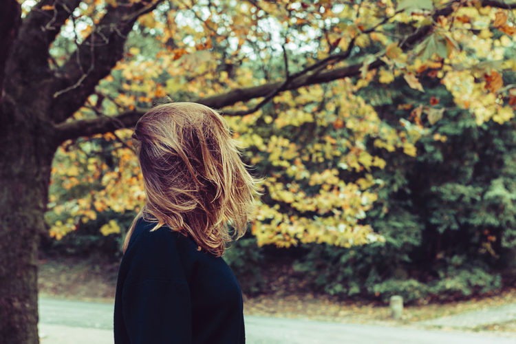 No face portrait of a woman with beautiful blond long hair and yellow leaves in background