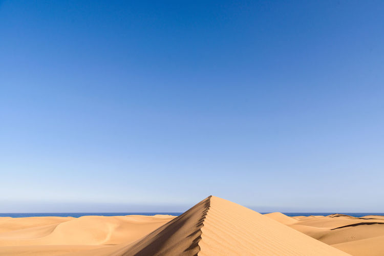 Low angle view of sand dunes against the sky at maspalomas on gran canaria