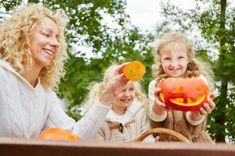 Happy Woman With Daughters Holding Pumpkins
