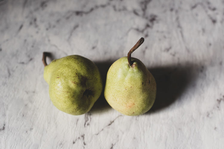 Green pears on grey marbled background Fruit Healthy Eating Food Food And Drink Freshness Wellbeing Still Life Close-up Table No People Pear Indoors  Green Color Focus On Foreground Two Objects High Angle View Ripe Day Juicy Plant