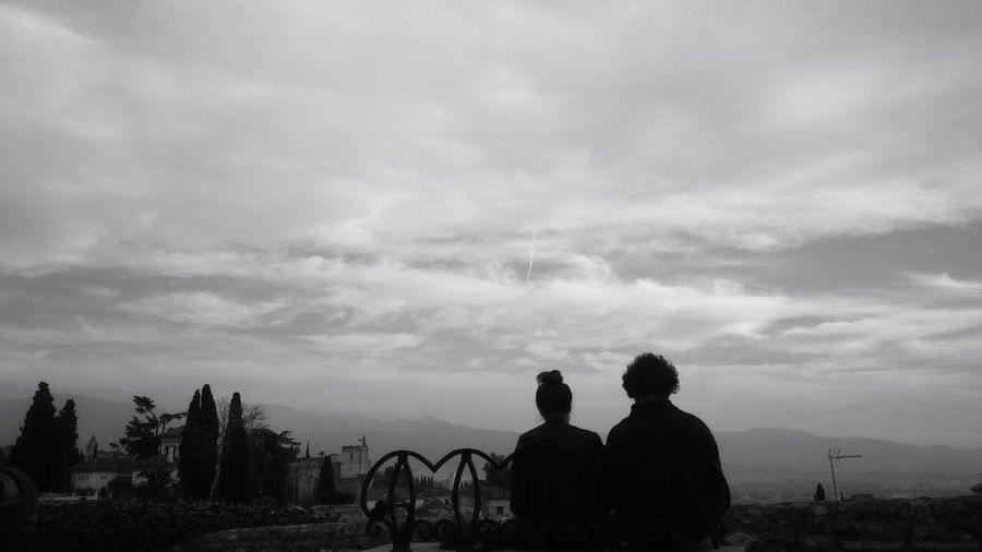 Silhouette men with people in background against sky